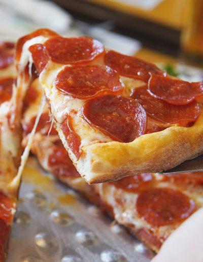 Slice of pepperoni pizza on spatula
