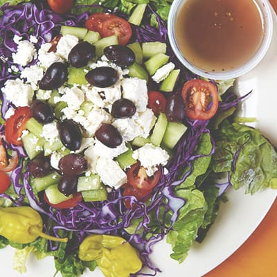 greek salad on plate with side of dressing